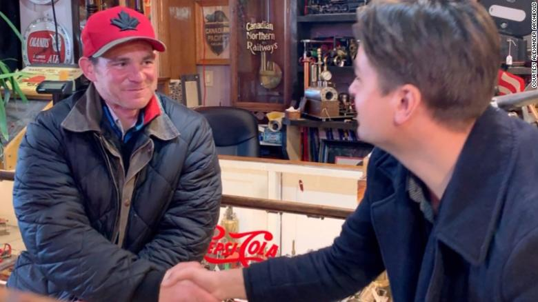 Adam Gillian, left, shakes hands with antique dealer Alexander Archbold.