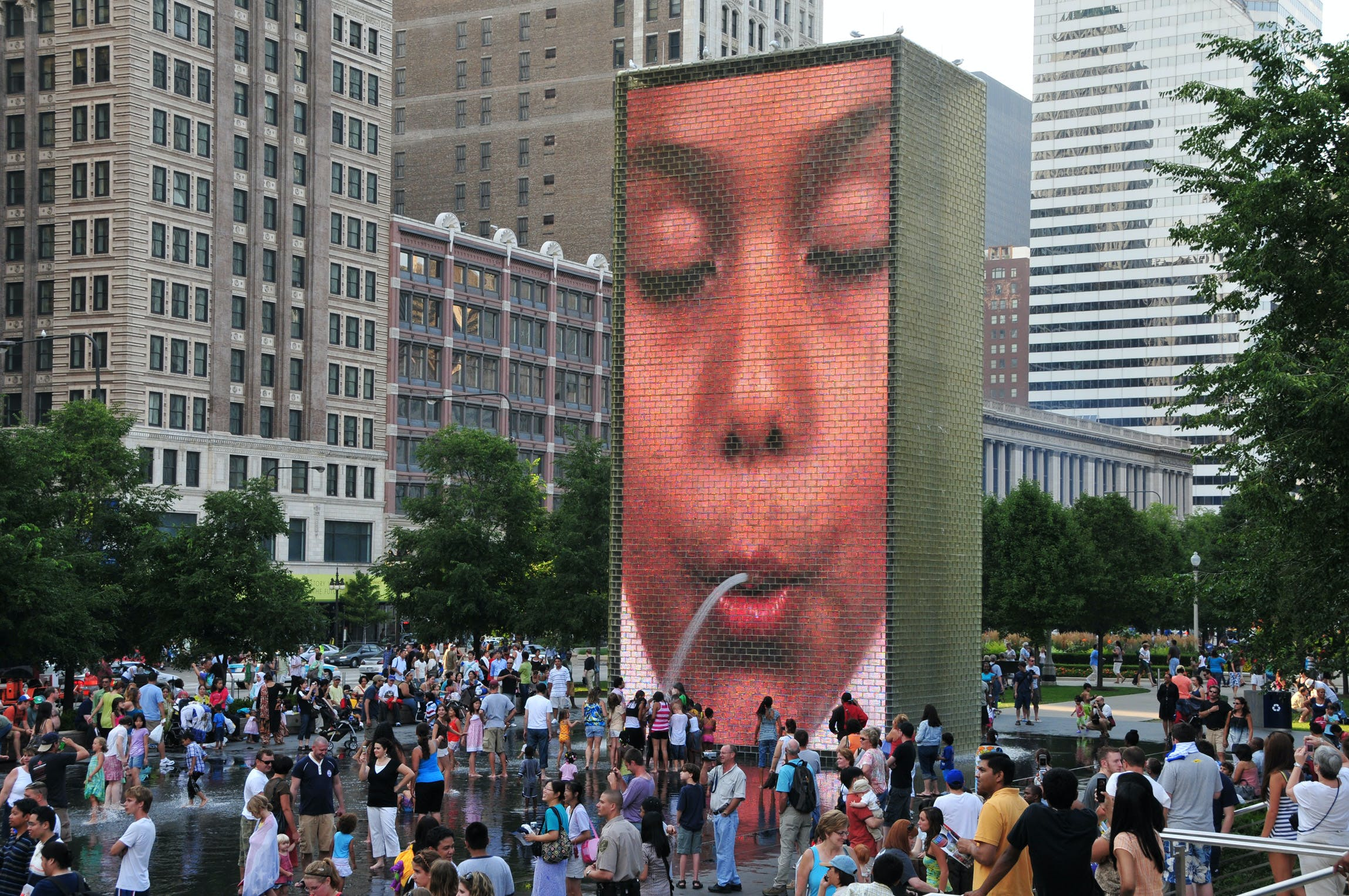 """A crowd gathers around Crown Fountain in Chicago's Millenium Park, where a fountain appears to """"spit"""" water on visitors."""