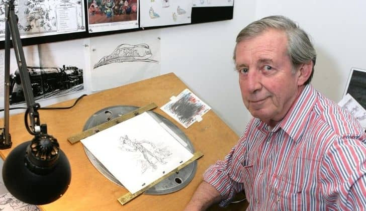 A photo of Bud Luckey who created Woody. On the table in front of him is an illustration of Woody